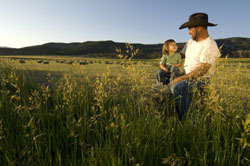 farmer with son in hay field