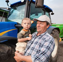 Farmer and son in front of a tractor
